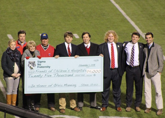 Epsilon Xi Chapter presents a $25,000 check to Friends of Children's Hospital in honor of Olivia Manning at halftime of the Auburn at Ole Miss football game.