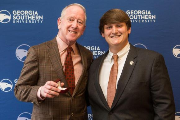 Theta Kappa Commander Adam Clay presents Sigma Nu Hall of Fame member and former NFL quarterback Archie Manning (Mississippi) with a Sigma Nu alumni lapel pin. Manning was on campus at Georgia Southern as part of the Leadership Lecture Series presented by the student affairs office. Photo courtesy of Jeremy Wilburn – Georgia Southern University.